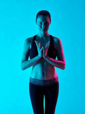one caucasian woman zen portrait namaste salte yoga  in silhouette studio isolated on blue background photo