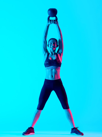 exercices: one mixed races woman exercsing Kettle Bell fitness exercices isolated on blue blackground