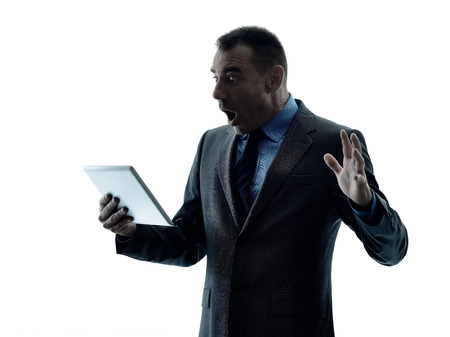one caucasian business man standing using digital tablet  silhouette isolated on white background photo