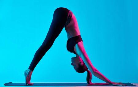 one caucasian woman exercising yoga Adho Mukha Svanasana exercices  in silhouette studio isolated on blue background photo