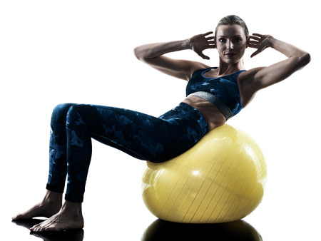 one caucasian woman exercising fitness swiss ball excercises in silhouette isolated on white background Standard-Bild