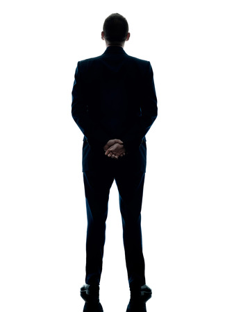 one caucasian business man standing rear view silhouette isolated on white background photo