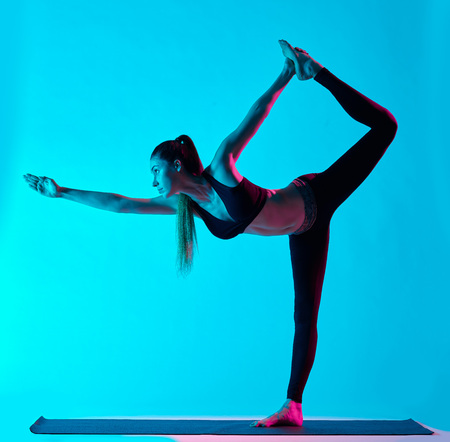 one caucasian woman exercising Natarajasana dancer pose yoga exercices  in silhouette studio isolated on blue background photo