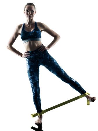 흰색 배경에 고립 된 실루엣에서 피트 니스 탄성 excercises 운동 한 백인 여자