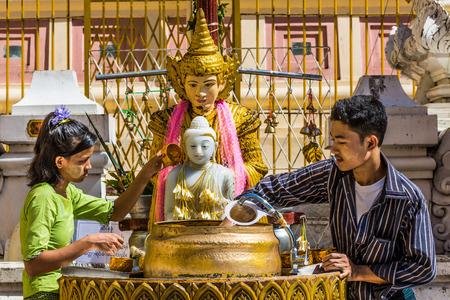 YANGON, MYANMAR - DECEMBER 16, 2016 : watering buddha statue Shwedagon Pagoda Yangon (Rangoon) in Myanmar (Burma)