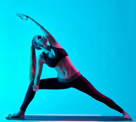 one caucasian woman exercising Utthita Parsvakonasana yoga exercices  in silhouette studio isolated on blue background photo