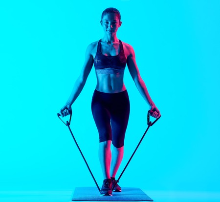one mixed races woman exercsing fitness elastics  exercices isolated on blue blackground 版權商用圖片