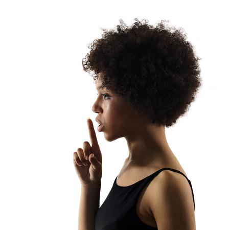 Een gemengd ras Afrikaanse jonge tiener meisje vrouw Hushing portret in studio schaduw silhouet geïsoleerd op een witte achtergrond Stockfoto - 82962163