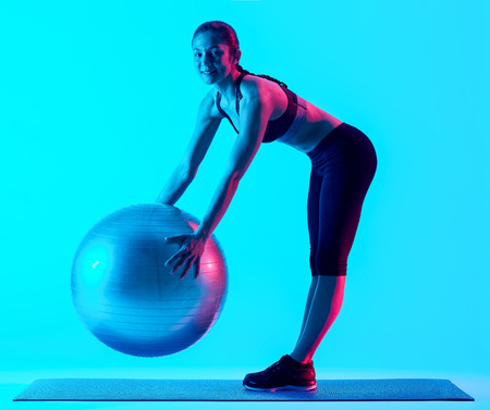 one mixed races woman exercsing fitness pilates exercices isolated on blue blackground photo