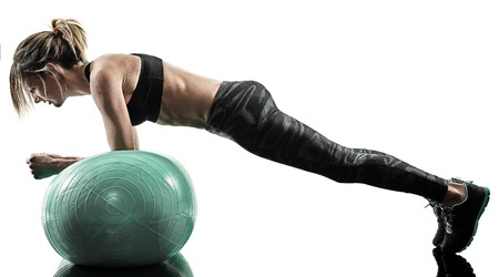 one caucasian woman exercising pilates fitness swiss ball exercises isolated  silhouette on white background 写真素材