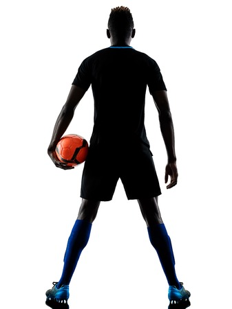 白い背景に隔離されたスタジオで遊んでいる1人のアフリカのサッカー選手の男 写真素材