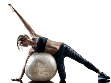 one caucasian woman exercising pilates fitness swiss ball exercises isolated  silhouette on white background Stock Photo