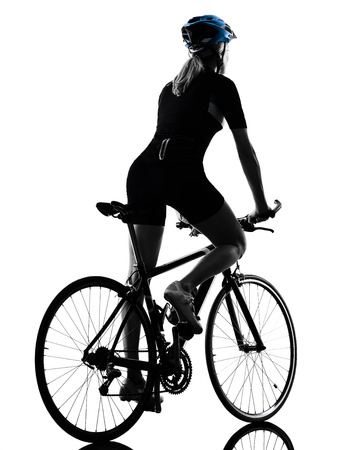 one caucasian cyclist woman cycling riding bicycle in silhouette isolated on white background rear view Stock Photo
