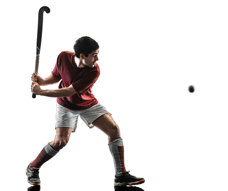 one caucasian field hockey player man isolated silhouette on white background Фото со стока