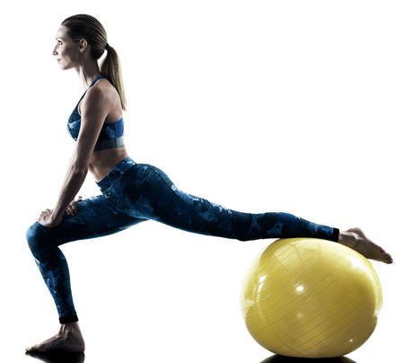 one caucasian woman exercising fitness swiss ball excercises in silhouette isolated on white background Stock Photo
