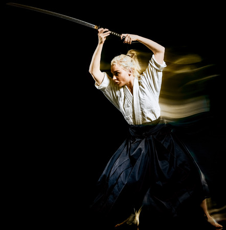 one bodokas fighters woman practicing Iaido  Kenjutsu  studio shot isolated on black background 版權商用圖片