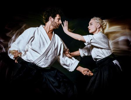 Deux combattants bodokas homme et femme pratiquant l'Aikido tourné en studio isolé sur fond noir Banque d'images