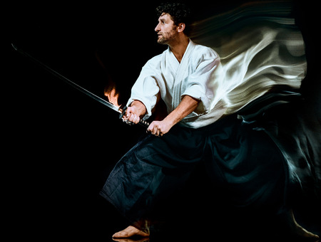 one caucasian bodoka fighters man practicing Iaido  Kenjutsu studio shot isolated on black background Stock Photo