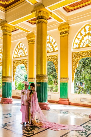 YANGON, MYANMAR - DECEMBER 16, 2016 : Burmese bride and groom posing with traditional cosutmes Shwedagon Pagoda Yangon (Rangoon) in Myanmar (Burma) Editorial