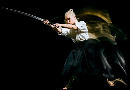 one bodokas fighters woman practicing Iaido  Kenjutsu  studio shot isolated on black background Banco de Imagens