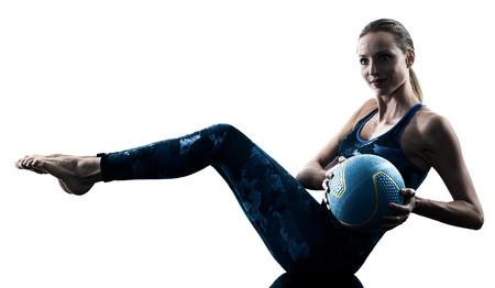 Una mujer caucásica ejercicio de fitness Medicine Ball ejercicios en silueta aislado sobre fondo blanco.