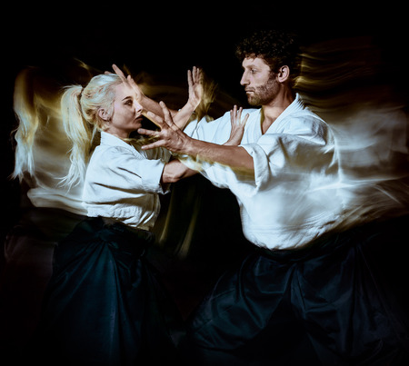 two bodokas fighters man and woman practicing Aikido studio shot isolated on black background