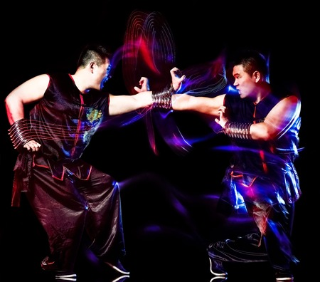 wushu chinese boxing kung fu Hung Gar fighter isolated man isolated on black background with speed light painting effect motion blur Stock Photo