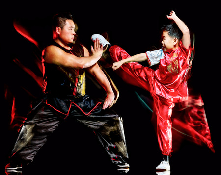 wushu chinese boxing kung fu Hung Gar fighter isolated child and man isolated on black background with speed light painting effect motion blur Banque d'images - 118624539