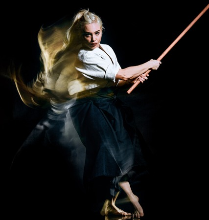 one caucasian bodoka fighters woman practicing Bo-Jutsu studio shot isolated on black background