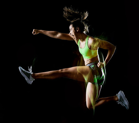 una donna di razza mista che esercita esercizi di fitness isolati su sfondo nero con effetto lightpainting Archivio Fotografico