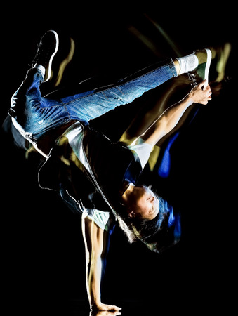 Un joven chino hip hop break dancer bailando aislado sobre fondo negro con efecto de pintura de luz de velocidad desenfoque de movimiento Foto de archivo