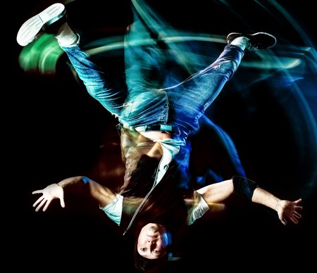one chinese young man hip hop break dancer dancing isolated on black background with speed light painting effect motion blur Stock Photo