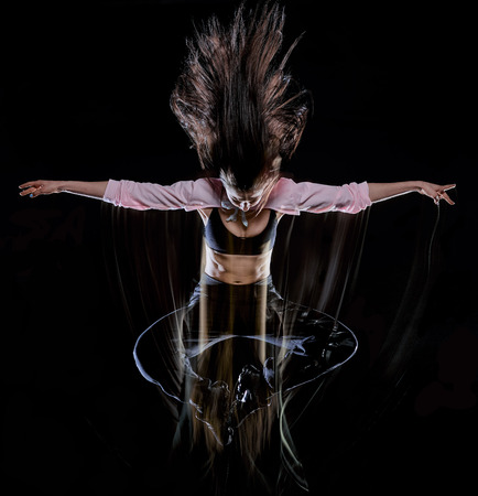 one caucasian young woman modern  dancer dancing isolated on black background with  light painting motion blur speed effect Banque d'images - 121655911