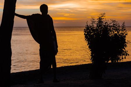 Masai man looking at sunset over the sea at Kizimkazi in Unguja aka Zanzibar Island Tanzania East Africa