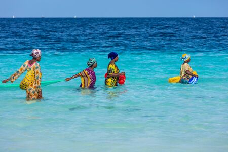 Kendwa, Zanzibar-March 4, 2019 : women in traditional clothing with fishing net into the sea at Kendwa beach 에디토리얼