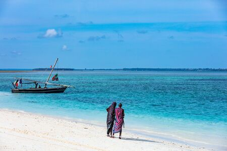 Kendwa, Zanzibar-March 4, 2019 : Masai people looking at boat on Kendwa beach