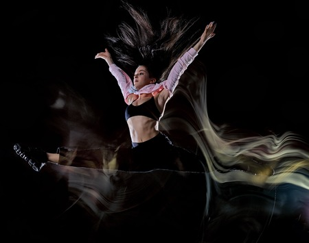 one caucasian young woman modern  dancer dancing isolated on black background with  light painting motion blur speed effect Banque d'images - 123145781