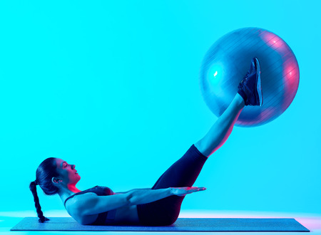 one mixed races woman exercsing fitness pilates exercices isolated on blue blackground 스톡 콘텐츠