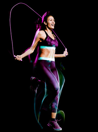 one beautiful caucasian mixed race woman exercising  jumping rope fitness exercises in studio isolated on black background