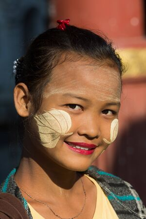 Mandalay, Myanmar - November 30, 2016 : one young burmese smiling woman portrait face wearing Thanaka traditional make up in Myanmar