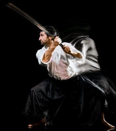 one caucasian bodoka fighters man practicing Iaido  Kenjutsu studio shot isolated on black background 版權商用圖片