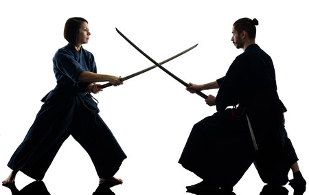 caucasian man and woman practicing laido Katori Shinto ryu isolated shadow silhouette on white background Stock Photo