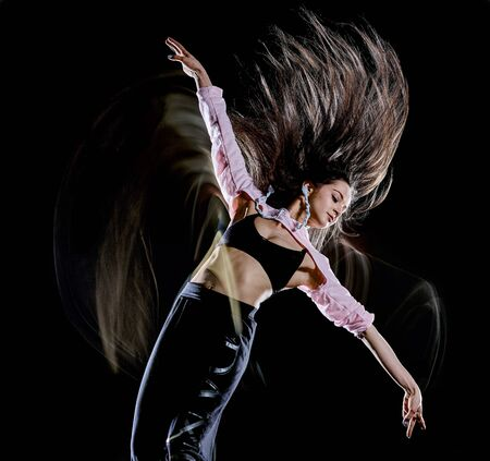 one caucasian young woman modern  dancer dancing isolated on black background with  light painting motion blur speed effect 免版税图像