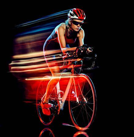 Eine kaukasische Frau Triathlon Triathlet Radfahrer Radfahren Studioaufnahme isoliert auf schwarzem Hintergrund mit Lichtmalerei-Effekt Standard-Bild