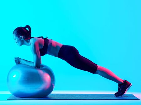 one mixed races woman exercsing fitness pilates exercices isolated on blue blackground Stok Fotoğraf