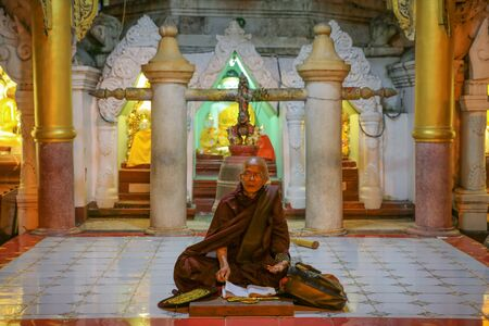 YANGON, MYANMAR -NOVEMBER 25, 2016 : monks praying at Shwedagon Pagoda Yangon in Myanmar