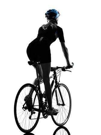 Una mujer caucásica ciclista ciclismo montando bicicleta en silueta aislado sobre fondo blanco vista trasera Foto de archivo