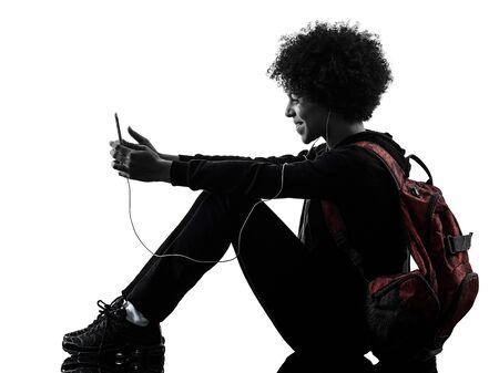 una donna africana della ragazza del giovane adolescente della corsa mista che utilizza telefono nella siluetta dell'ombra dello studio isolata su fondo bianco