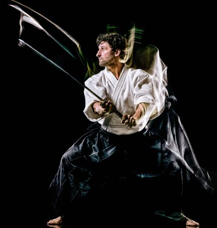 one caucasian bodoka fighters man practicing Iaido Kenjutsu studio shot isolated on black background Stock Photo - 131845736