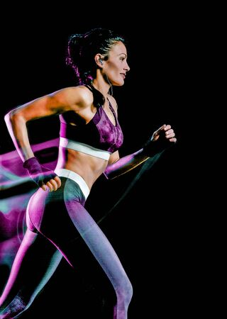 one beautiful caucasian mixed race woman unner jogger jogging running in studio isolated on black background Standard-Bild